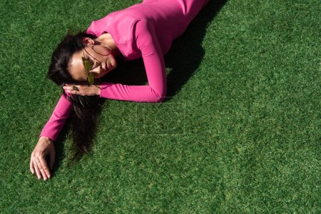 high angle view of attractive woman in dress and sunglasses posing and lying on grass outside