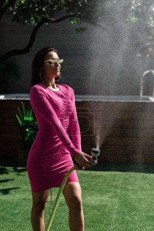 attraktive Frau in Kleid und Sonnenbrille posiert mit Wasserschlauch draußen