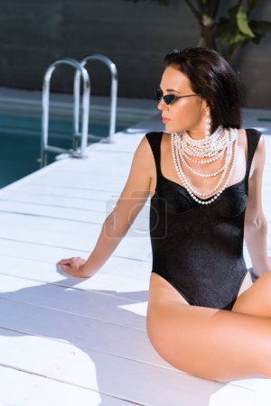 Photo pour Attractive woman in black swimsuit and sunglasses posing outside - image libre de droit