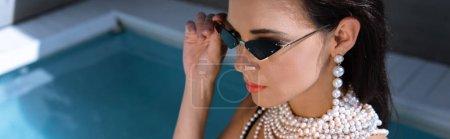 Photo pour Plan panoramique de femme séduisante en lunettes de soleil posant près de la piscine - image libre de droit