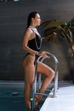 Photo pour Vue latérale de la femme attrayante en maillot de bain noir et collier de perles posant dans la piscine - image libre de droit