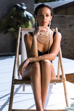 Photo pour Attrayant femme en maillot de bain noir et collier de perles posant et assis sur chaise longue - image libre de droit