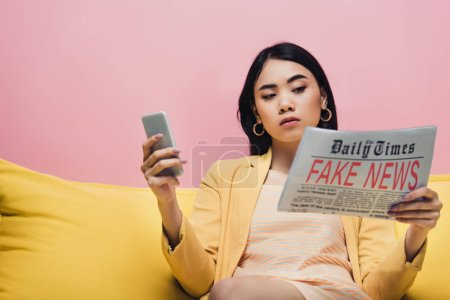 ernsthafte Asiatin hält Zeitung mit Fake News und Smartphone auf gelbem Sofa isoliert auf rosa