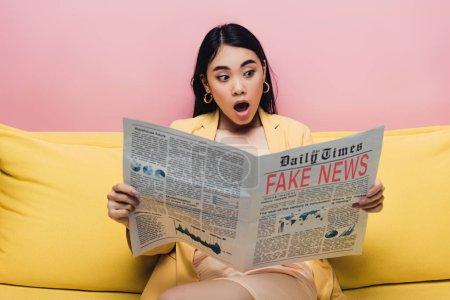 Photo pour Choqué asiatique femme tenue journal avec faux nouvelles isolé sur rose - image libre de droit
