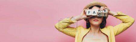 Photo pour Plan panoramique de femme asiatique tenant des cubes en bois devant le visage avec faux lettrage et fait isolé sur rose - image libre de droit