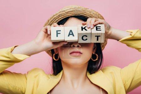 Photo pour Asiatique femme tenant en bois cubes en face de visage avec faux et fait lettrage isolé sur rose - image libre de droit