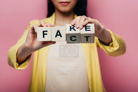 Photo pour Vue recadrée de femme asiatique tenant des cubes en bois avec faux et fait lettrage isolé sur rose - image libre de droit