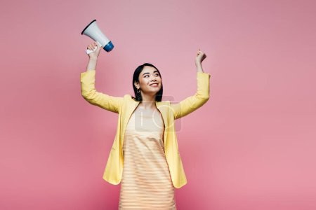 Photo for Happy asian woman in yellow outfit holding megaphone isolated on pink - Royalty Free Image