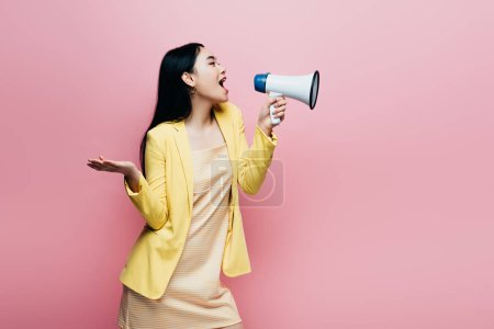 Photo pour Side view of asian woman in yellow outfit screaming in megaphone isolated on pink - image libre de droit