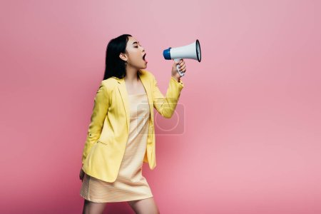Photo for Side view of asian woman in yellow outfit screaming in megaphone isolated on pink - Royalty Free Image