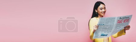 Photo for Panoramic shot of happy asian woman in yellow outfit reading newspaper with fake news isolated on pink - Royalty Free Image
