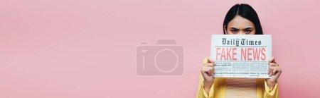 Photo pour Triste asiatique femme en jaune tenue tenue journal avec faux nouvelles isolé sur rose, panoramique shot - image libre de droit