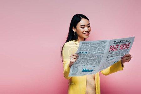 Photo pour Heureux asiatique femme dans jaune tenue lecture journal avec faux nouvelles isolé sur rose - image libre de droit