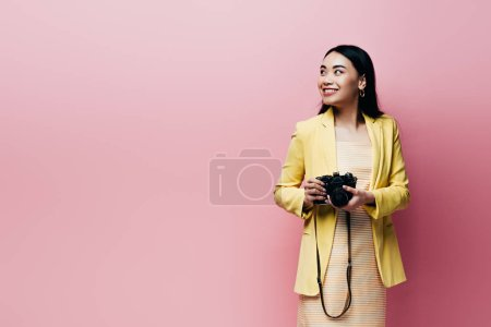 smiling asian woman in yellow outfit holding digital camera and looking away isolated on pink
