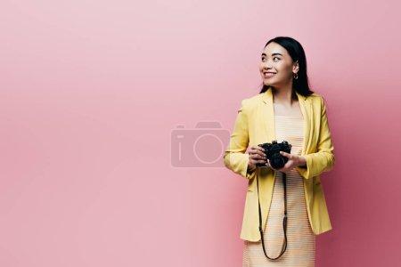 Photo pour Souriant asiatique femme en jaune tenue tenant appareil photo numérique et regardant loin isolé sur rose - image libre de droit