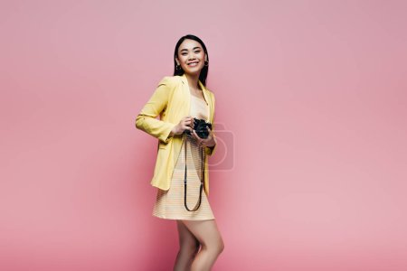 Photo for Happy asian woman in yellow outfit holding digital camera isolated on pink - Royalty Free Image