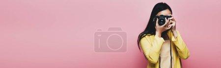Photo pour Femme asiatique en costume jaune prise de photo sur un appareil photo numérique isolée sur une photo panoramique rose - image libre de droit