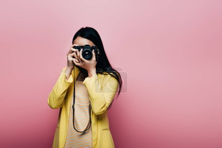 Photo for Asian woman in yellow outfit taking picture on digital camera isolated on pink - Royalty Free Image