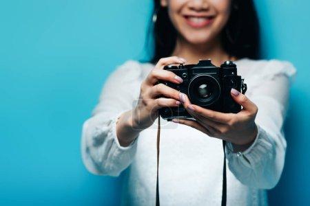 Photo pour Vue recadrée de sourire femme asiatique en chemisier blanc tenant appareil photo numérique sur fond bleu - image libre de droit