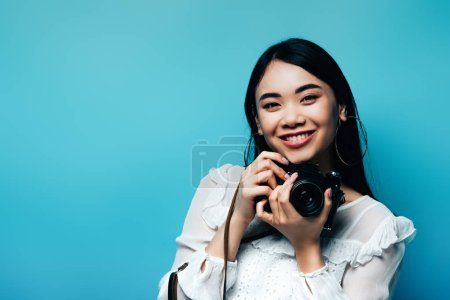 Photo pour Happy asian woman in white blouse holding digital camera on blue background - image libre de droit