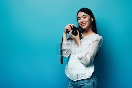 Photo pour Heureux asiatique femme en blanc chemisier tenant appareil photo numérique sur fond bleu - image libre de droit