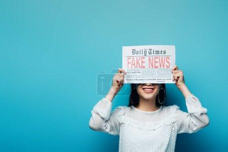 Photo pour Souriant asiatique femme en chemisier blanc tenant journal avec de fausses nouvelles sur fond bleu - image libre de droit