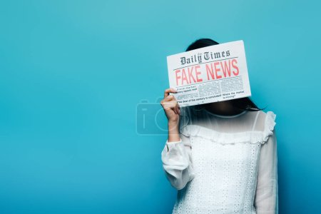 Photo for Woman in white blouse holding newspaper with fake news on blue background - Royalty Free Image
