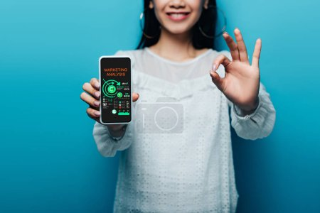 Photo for Cropped view of smiling asian woman in white blouse showing ok sign and smartphone with marketing analysis app on blue background - Royalty Free Image
