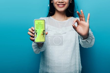 Photo pour Vue croisée d'une femme asiatique souriante en blouse blanche montrant un signe ok et un téléphone intelligent avec la meilleure application de magasinage sur fond bleu - image libre de droit