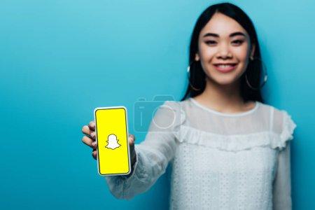 Photo pour KYIV, UKRAINE - 15 JUILLET 2019 : mise au point sélective de la femme asiatique souriante en chemisier blanc tenant smartphone avec application snapchat sur fond bleu - image libre de droit