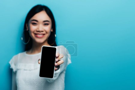 Photo for Selective focus of smiling asian woman in white blouse holding smartphone with blank screen on blue background - Royalty Free Image