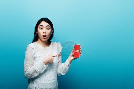 Photo pour KYIV, UKRAINE - 15 JUILLET 2019 : femme asiatique choquée pointant du doigt son smartphone avec l'application youtube sur fond bleu - image libre de droit