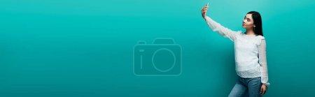 Photo pour Femme asiatique en chemisier blanc prenant selfie sur smartphone sur fond turquoise, plan panoramique - image libre de droit