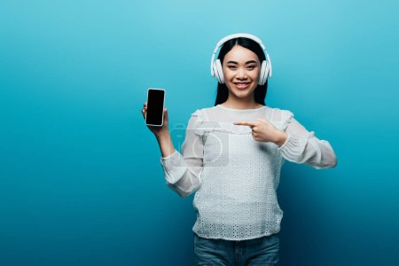 Photo pour Souriant asiatique femme avec casque pointant du doigt à smartphone avec écran blanc sur fond bleu - image libre de droit