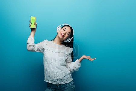 Photo pour Une asiatique souriante aux yeux fermés dans un casque d'écoute tenant un smartphone avec la meilleure application pour faire ses courses et dansant sur fond bleu - image libre de droit