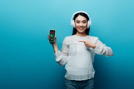 Photo for Smiling asian woman with headphones pointing with finger at smartphone with marketing analysis app on blue background - Royalty Free Image