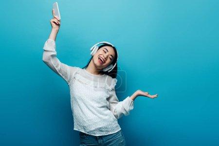 Photo pour Une femme asiatique souriante, les yeux fermés dans des écouteurs tenant un smartphone et dansant sur fond bleu - image libre de droit