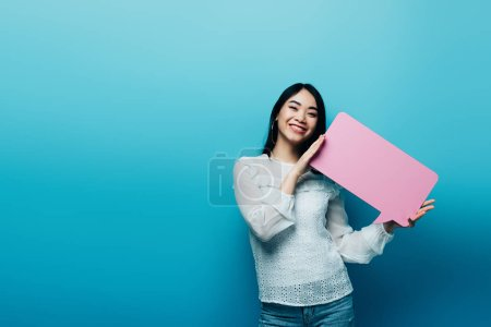 Photo for Cheerful brunette asian woman holding pink speech bubble on blue background - Royalty Free Image