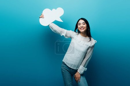 Photo pour Sourire brunette asiatique femme tenant vide pensée bulle sur fond bleu - image libre de droit