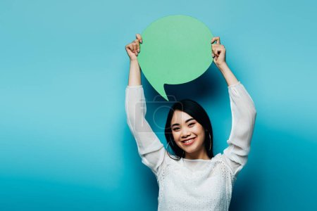 smiling brunette asian woman holding green speech bubble on blue background