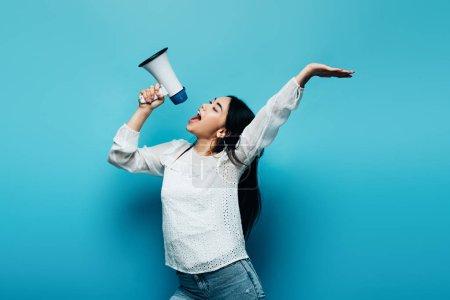 Photo pour Brunette asiatique femme crier dans haut-parleur sur fond bleu - image libre de droit