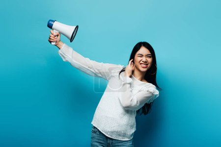 brunette asian woman holding loudspeaker on blue background