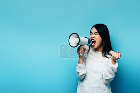 Photo for Angry brunette asian woman screaming in loudspeaker on blue background - Royalty Free Image