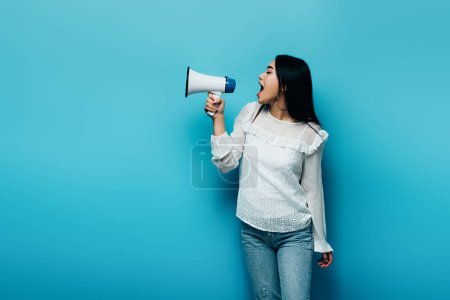 Photo for Brunette asian woman screaming in loudspeaker on blue background - Royalty Free Image