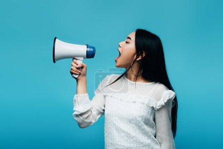 Photo pour Brune asiatique criant dans un haut-parleur sur fond bleu - image libre de droit
