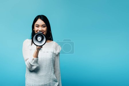 Photo for Smiling brunette asian woman holding loudspeaker on blue background - Royalty Free Image