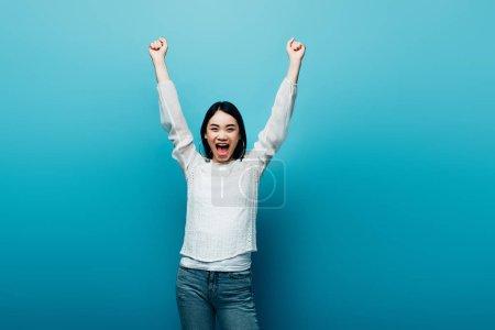 Photo pour Heureux brunette asiatique femme avec les mains dans l'air sur fond bleu - image libre de droit