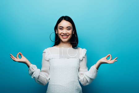 Photo pour Belle brune asiatique méditant sur fond bleu - image libre de droit