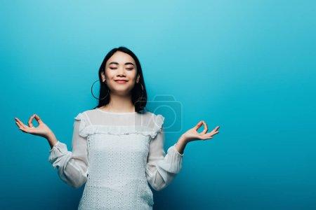 Photo pour Jolie brune asiatique méditant les yeux fermés sur fond bleu - image libre de droit