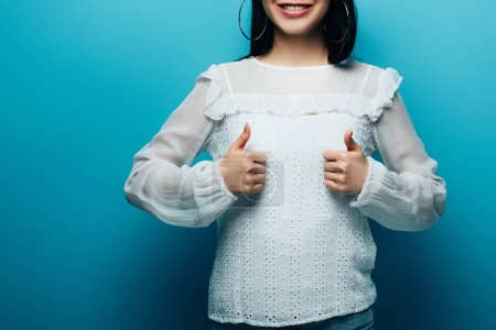 Photo for Cropped view of happy brunette asian woman showing thumbs up on blue background - Royalty Free Image
